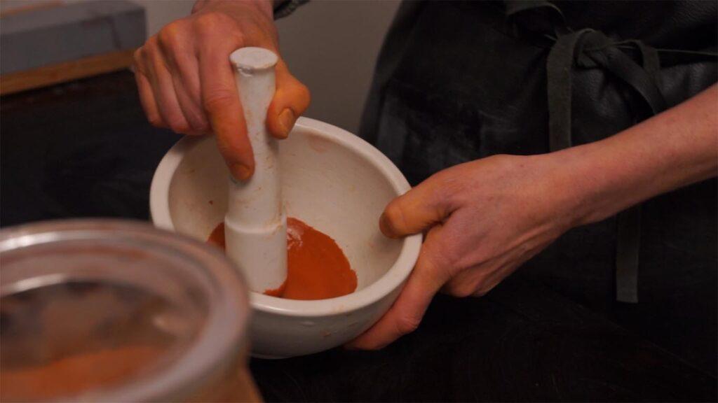 Naturlig orange farve knuses i morter, så pigmentet kan bruges til fremstilling af pastelkridt