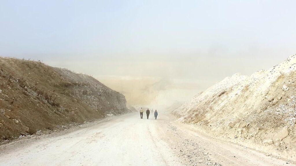 Tre mennesker set fra ryggen gående i kridtbrud nær Stevns Klint